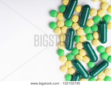 A Top View Of A Heap Of Yellow And Green Medicine Pills And Capsules On White Surface.
