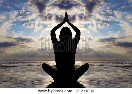Seated yoga pose on the beach at sunset.