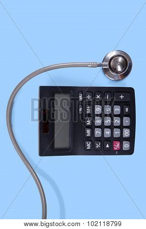 Calculator And Stethoscope On Blue Background