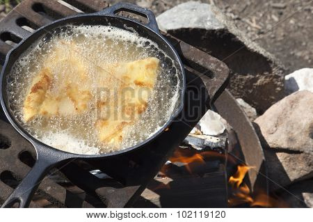 Fish Frying In A Cast Iron Pan On An Outdoor Grill