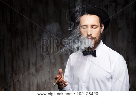 Attractive young bearded guy with hat and cigarette