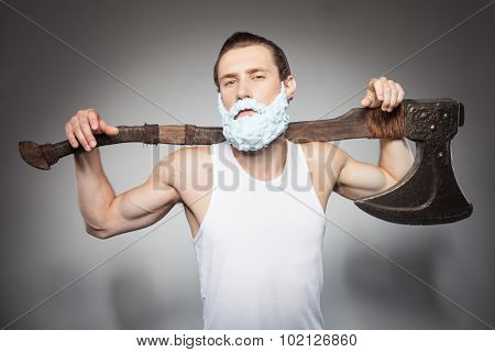 Attractive young hipster man is boasting of his hatchet
