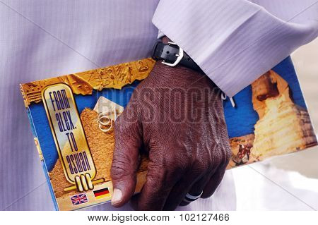 Nubian Egyptian man holds Egyptian Tour Guide Map in Aswan Egypt.