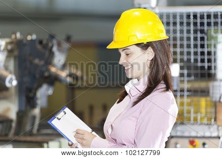 Mechanical engineer taking notes at metallurgy factory poster