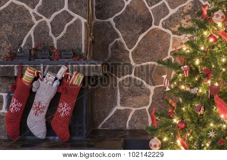 Stockings hanging on a fireplace next to a christmas tree on christmas morning