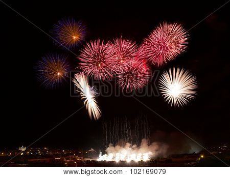 Fireworks in noisy background.Colorful fireworks in Malta with house light in the far, Malta firewor