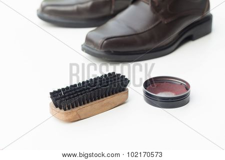 Dark brown shoe with shoe polish and brush shoe isolated on white background poster