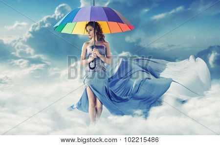 Brunette beauty walking with an umbrella in the clouds