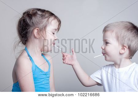 siblings having fun with lollypops - little brother is trying to grab his sister's lollypop