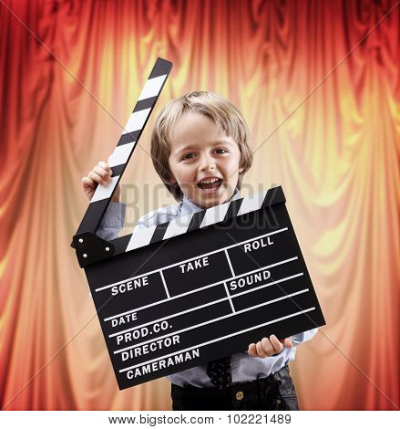 Boy holding a blank clapper board in a cinema theater concept for movie, action, film industry or theatrical performance