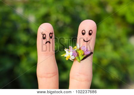 Finger art of couple. Joyful man gives a woman a bouquet of flowers, it is not satisfied.