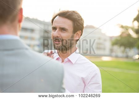 Businessman conversing with colleague at park on sunny day poster