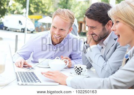 Cheerful businesspeople using laptop together at sidewalk cafe