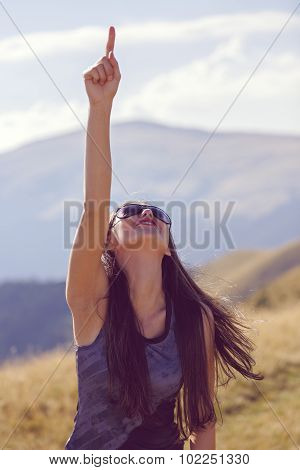 Beautiful And Happy Woman Pointing Skyward
