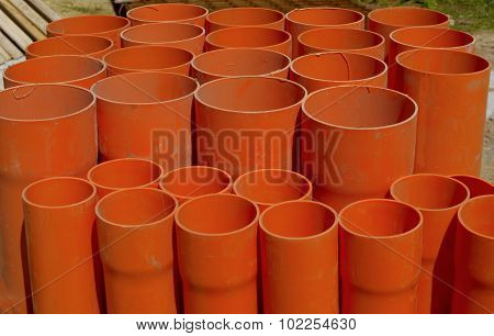 A bundle of red pvc pipes