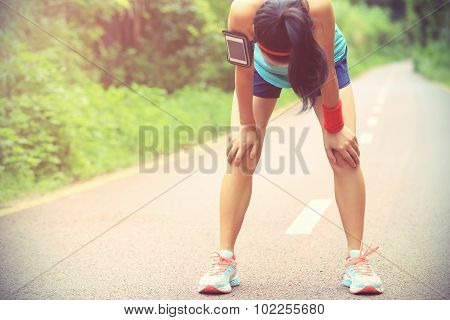 tired woman runner taking a rest after running hard