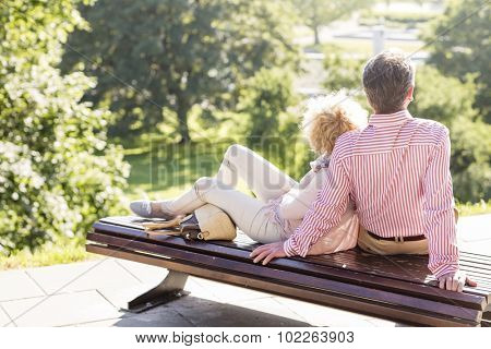 Middle-aged couple relaxing on park bench