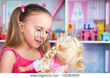 Pretty little girl playing with doll