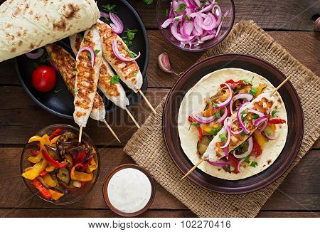 Chicken kebab with grilled vegetables and tortilla wrap.