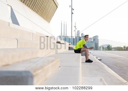 Young runner taking break after workout training outdoors