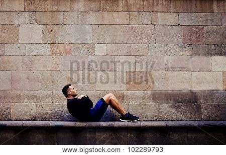 Sporty guy engaged an intensive fitness training in urban setting