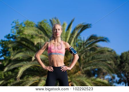 Athletic female with slender body taking break after fitness training outdoors