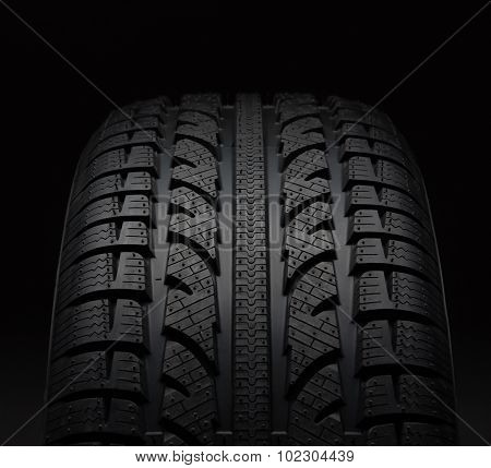 Close-up Of Car Tire Over Black Background