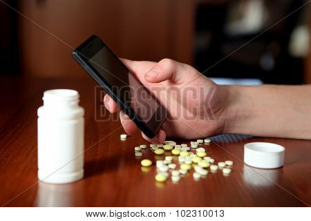 Person With Cellphone And Pills