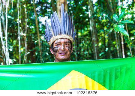 Native Brazilian man holding the Brazilian flag in the jungle in Amazon
