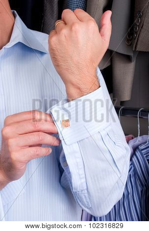 A man putting on his cuff links