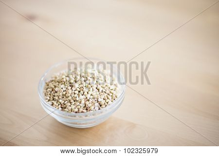 Bowl of buckwheat groats on wooden table