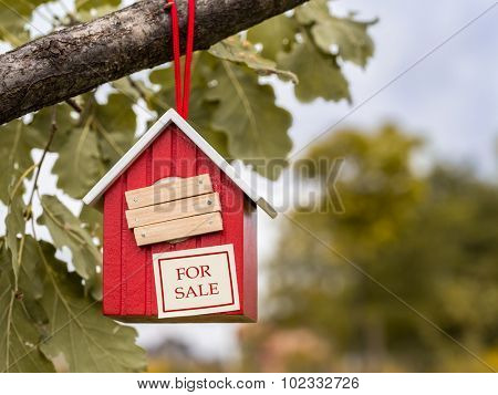 Wooden red birdhouse hanging on tree branch with entry hole covered with planks and note FOR SALE attached to it