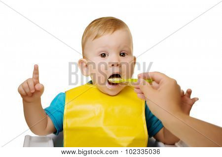 Baby eating spoon baby food jar.  Child feeding. Giving fruit sauce to baby boy. Child sitting in chair with a spoon Spoon-feeds the child