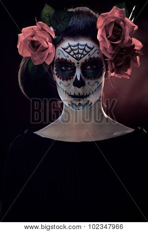 Portrait of scary spooky woman at halloween santa muerte makeup.