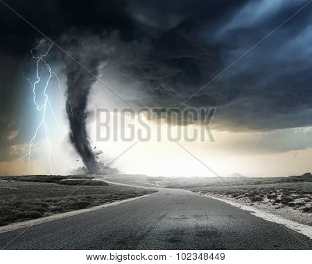Black tornado funnel and lightning on road