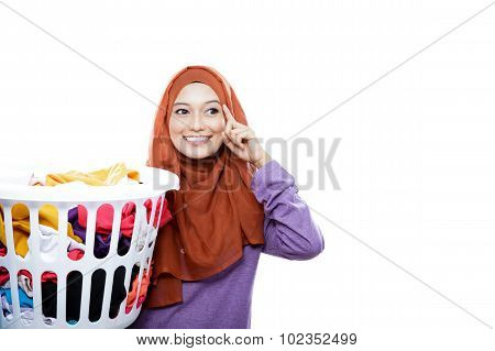 portrait of beautiful woman wearing hijab carrying laundry basket with hand in her heads pretend to thinking with copy space isolated on white poster