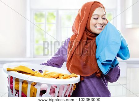 portait of young woman wearing hijab carrying laundry basket while smelling fresh clean clothes poster