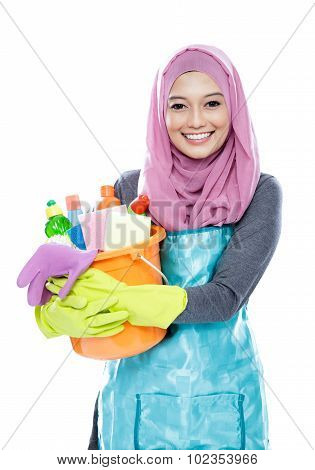 portrait of housewife wearing hijab holding bucket full of cleaning supplies isolated on white background poster
