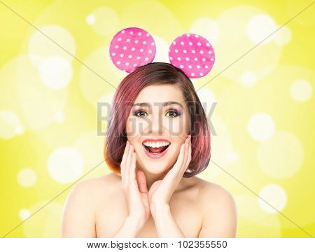 Beautiful young smiling woman in mickey mouse ears on bubble background.