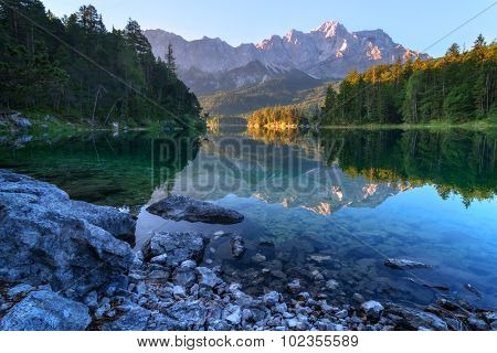 Fantastic sundown on mountain lake Eibsee, located in the Bavaria, Germany. Dramatic unusual scene. Alps, Europe.
