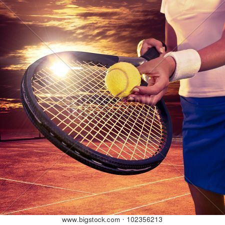 Female hands holding tennis  racket and ball on sky with sun.