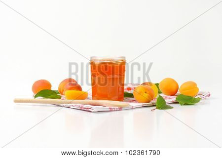 opened jar with apricot jam standing on the kitchen cloth with wooden spoon and fresh apricots