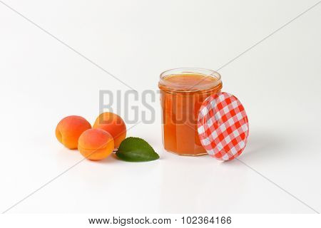 opened jar of apricot jam with three fresh apricot next to