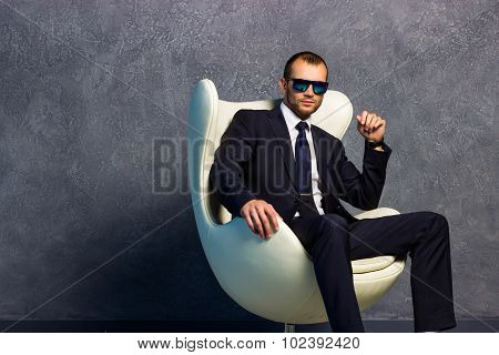 Brutal sexy businessmen in suit with tie and sunglasses sitting on chair. Boss concept.