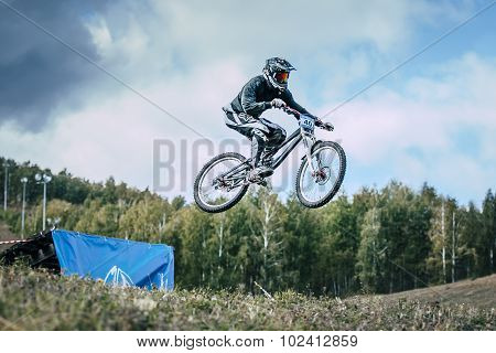 Athlete on a mountain bike is flying in a jump from a springboard