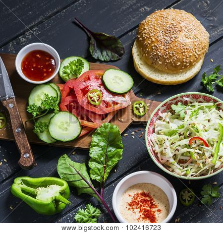 delicious veggie Burger. Raw ingredients - cabbage tomato cucumber lettuce pepper sauce vegetarian and a homemade bun for burgers on a dark wooden surface poster