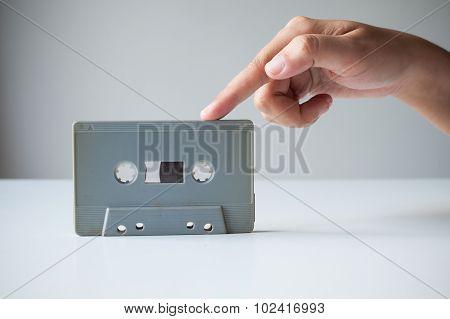Hand Point Finger On Old Retro Cassette Tape.