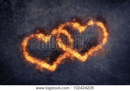 Couple of decorative overlapping flaming hearts with fiery orange flames for valentines day or a wedding, symbolic of love and romance, dark background with copyspace