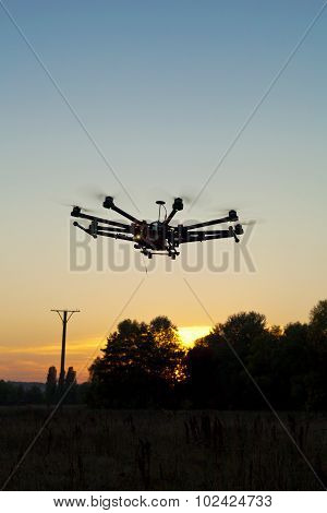 Drone on a background of a beautiful sunset. UAV in flight. Quadrocopters on radio. poster