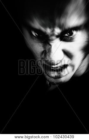 Evil face of scary angry man in the dark